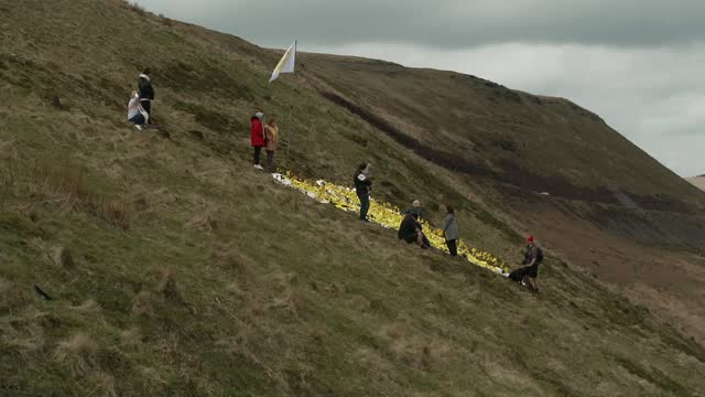 marks one year since the first lockdown; wales: south wales: ext air views / drone footage large yellow heart on hillside close shots flags and... - hill stock videos & royalty-free footage