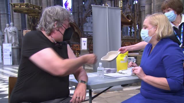 vídeos de stock e filmes b-roll de vaccination centre set up in westminster abbey; england: london: westminster abbey: int stephen fry being given covid-19 coronavirus vaccine jab and... - stephen fry