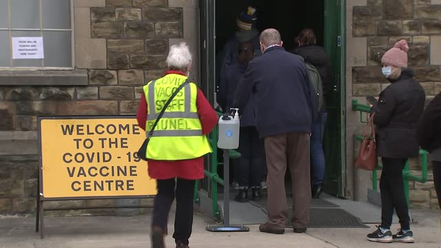 vaccine centre in swindon; england: wiltshire: swindon: ext queue of people wearing masks / people given hand sanitiser / patients entering... - wide stock videos & royalty-free footage