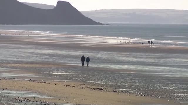 vídeos de stock e filmes b-roll de wales ban on travellers from covid hotspots across the uk comes into effect; wales: ext wide shot of empty beach few people along beach - país de gales