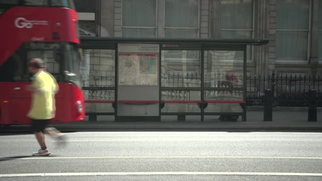 will public transport be made safe for commuters by wednesday england london westminster ext gv man running right to left and bus along left to right... - cycling stock videos & royalty-free footage