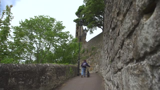 witness claims that dominic cummings was seen in barnard castle; england: durham: barnard castle: ext man pushing bicycle along up pathway towards... - durham england bildbanksvideor och videomaterial från bakom kulisserna