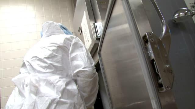 vidéos et rushes de a coroner prepares a metal slab during an autopsy. - charlotte médicale ou sanitaire