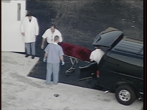coroners van backs up near coroners outside coroner's office as coroners remove celebrity anna nicole smith's covered body on gurney from the van to... - anna nicole smith stock videos & royalty-free footage