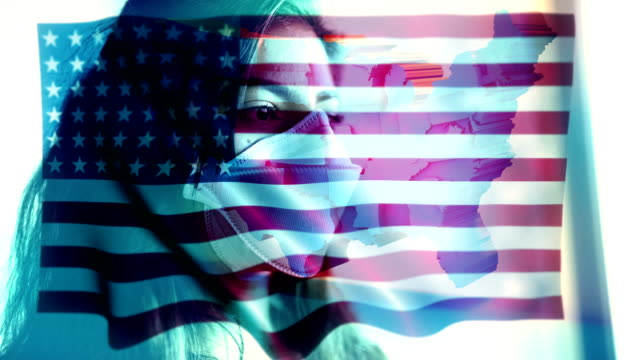 コロノウイルス 2019-ncov 背景概念.米国の旗のオーバーレイと保護マスクを身に着けている忍耐。 - rnaウイルス点の映像素材/bロール