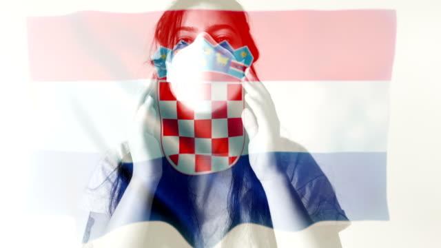 コロノウイルス 2019-ncov 背景概念.クロアチア国旗オーバーレイで保護マスクを着用した忍耐。 - rnaウイルス点の映像素材/bロール