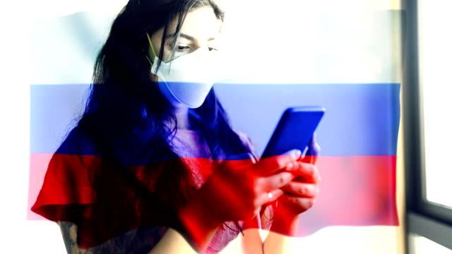 コロノウイルス 2019-ncov 背景概念.ロシアの旗のオーバーレイと保護マスクを身に着けている忍耐。 - rnaウイルス点の映像素材/bロール
