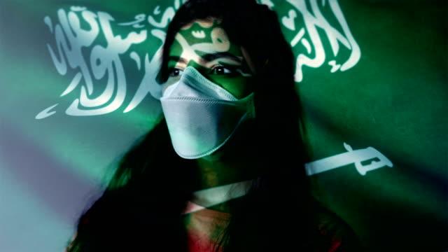 コロノウイルス 2019-ncov 背景概念.アラビア国旗オーバーレイと保護マスクを身に着けている忍耐。 - rnaウイルス点の映像素材/bロール