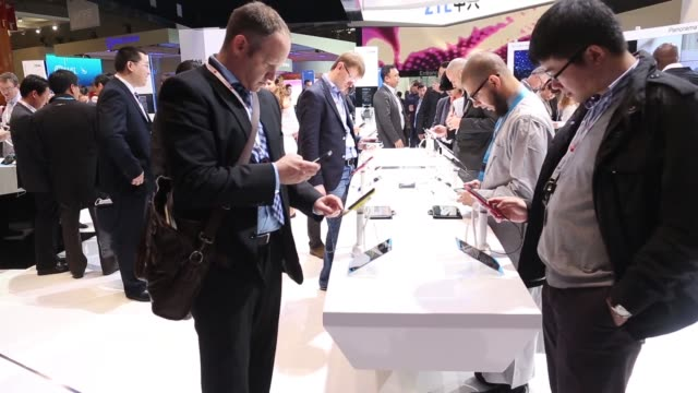corp. grand s smartphone on display at the mobile world congress in barcelona, visitors inspect zte corp. smartphones, zte corp. pavilion, visitors... - 3日目点の映像素材/bロール