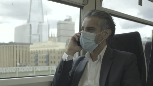 corporate business man commuting to work on the train wearing face mask and using smart phone - geschäftsreise stock-videos und b-roll-filmmaterial