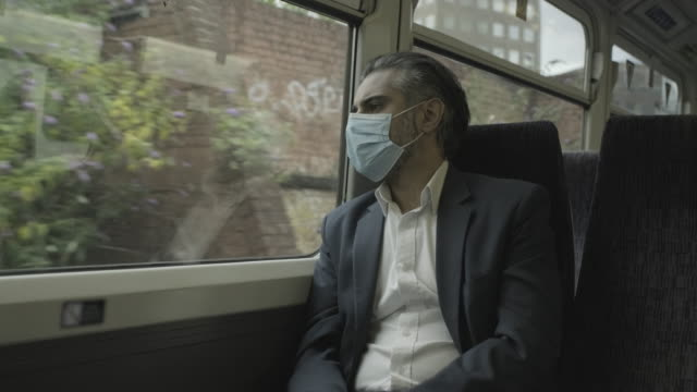 corporate business man commuting to work on the train wearing face mask and using smart phone and looking at view - grey hair stock videos & royalty-free footage