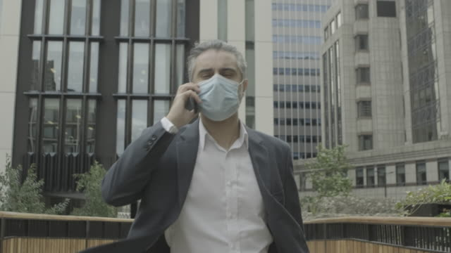 corporate business man commuting to work wearing face mask in the city of london during covid-19 pandemic - grey hair stock videos & royalty-free footage