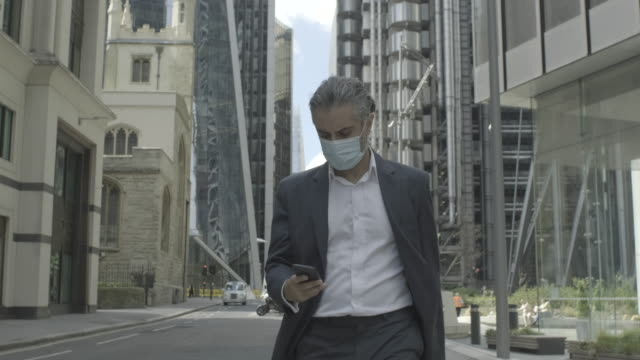 corporate business man commuting to work wearing face mask in the city of london during covid-19 pandemic - geschäftsreise stock-videos und b-roll-filmmaterial