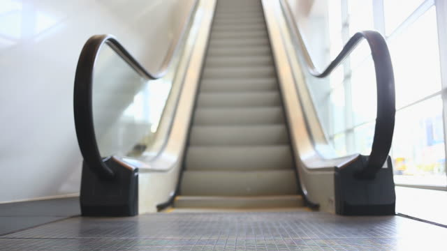 corporate couple on escalator - efficiency stock videos and b-roll footage