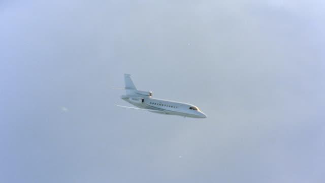 a corporate jet flies  above the clouds. - flugzeug in der luft stock-videos und b-roll-filmmaterial
