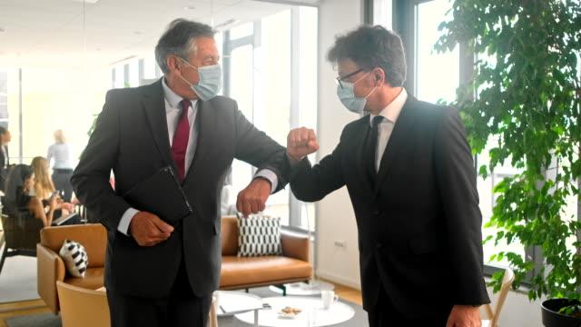 vídeos de stock, filmes e b-roll de profissionais corporativos cumprimentando com elbow bump após reunião de negócios durante covid-19 - cumprimentando