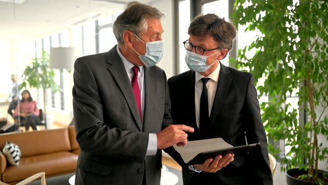 corporate professionals with protective face mask using digital tablet in office lobby during covid-19 - working seniors stock videos & royalty-free footage