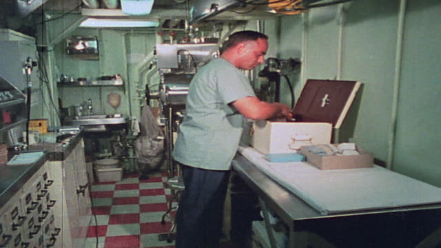 vídeos de stock, filmes e b-roll de corpsman in sickbay sorting through medicines stored in box marked with red cross aboard uss harnett county / vietnam - formato letterbox