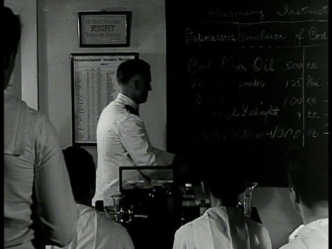 corpsman placing bottles on shelf vs instructor in pharmacy classroom ms blackboard w/ chemical names vs weighing powder mixing prescription wwii - hospital corpsman点の映像素材/bロール