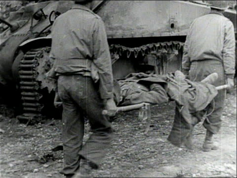 ts corpsmen carry wounded soldiers past destroyed german tank after the battle / san pietro italy - tank stock videos and b-roll footage
