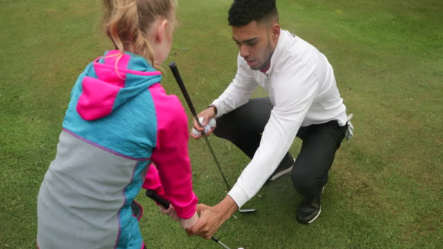 correcting young golfers grip - green golf course stock videos & royalty-free footage