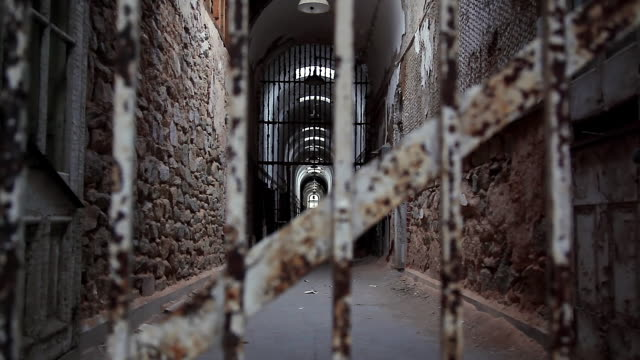 vídeos de stock, filmes e b-roll de ws corridor and prison bars of crumbling cell block / eastern state penitentiary historic site, philadelphia, pennsylvania, united states - grade de prisão