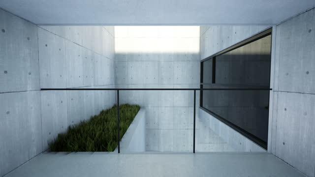 ein korridor mit betonwänden, die zu einem balkon führen, der von den strahlen der untergehenden sonne beleuchtet wird - beton stock-videos und b-roll-filmmaterial