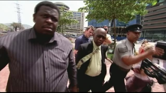 New bribery claims against Warner / UEFA meeting in Berlin TIRNIDAD AND TOBAGO Port of Spain EXT Various of police officers and a bodyguard shielding...