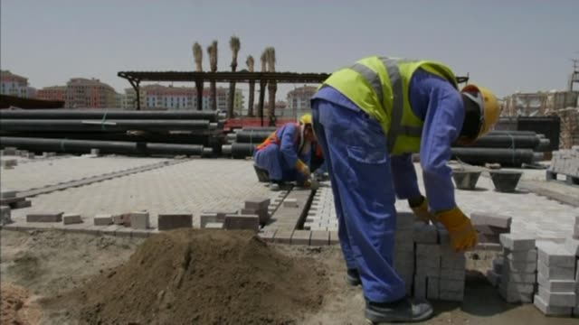 Threat from sponsors R04041420 / QATAR Doha Various of construction workers laying stone pavings
