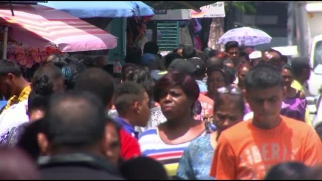 corruption scandal: view of jack warner in trinidad; people along through market woman shopper at stall people in market low angle view of market - trinidad trinidad and tobago stock videos & royalty-free footage
