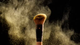 Cosmetic brush with golden cosmetic powder for make up