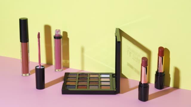 パステルの背景にライトペイントを使用した化粧品コレクション - シネマグラフ点の映像素材/bロール