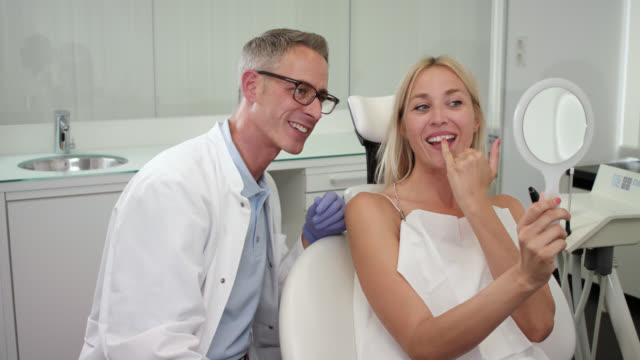 cosmetic dentistry, dentist with greying hair in white medical doctor's coat and female patient with blonde hair on chair, doctor shows woman the result of the dental treatment after cleaning odontexesis and whitening the teeth, takes off the serviette.