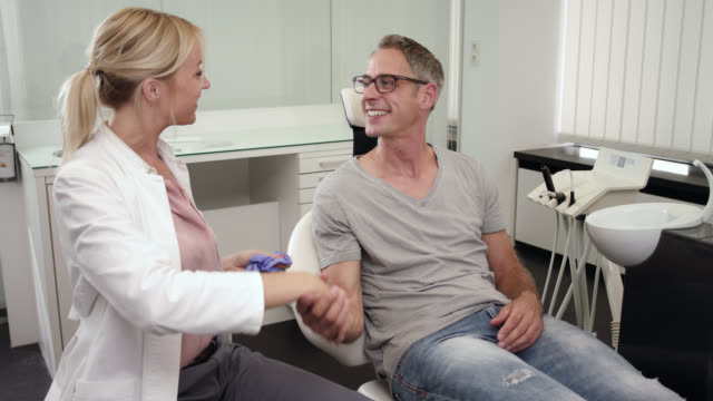 cosmetic dentistry dentist's office - female doctor dentist in doctor's white coat medical scrubs takes off gloves and says good bye to happy satisfied male patient with handshake after dental care, bleaching and professional tooth cleaning odontexesis. - glove stock videos and b-roll footage