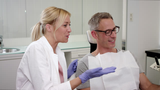 cosmetic dentistry dentist's office – male patient sits on chair after receiving dental care check up, teeth whitening bleaching and professional tooth cleaning, female doctor with long blonde hair wearing exam gloves shows man the result using a mirror - teeth whitening stock videos and b-roll footage