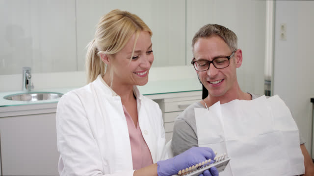 cosmetic dentistry dentist's office – male patient sitting on chair before receiving dental care check up and teeth whitening bleaching, female doctor with long blonde hair wearing exam gloves checks tooth color with a comparison veneer scale chart. - teeth whitening stock videos and b-roll footage