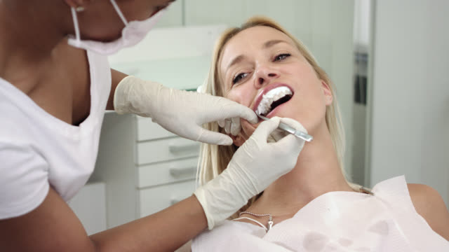 cosmetic dentistry dentist's office - women in her 30s with long blonde hair lying on chair receives dental care and after teeth whitening bleaching, female doctor wearing exam gloves removing upper gingiva protector with forceps. - teeth whitening stock videos and b-roll footage