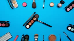Cosmetics set for women on blue paper background,top view stop motion animation timelapse