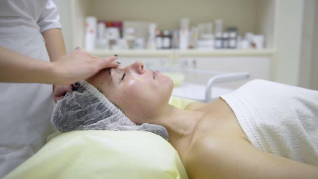 cosmetologist applying cream