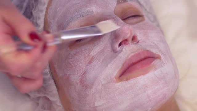 vídeos de stock, filmes e b-roll de cosmetologista aplicando nutrir a máscara facial de cosmética em salão de spa - tratamento de pele