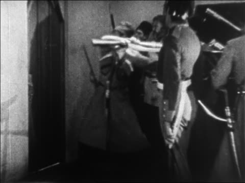 B/W 1925 Cossack guard banging on door with gun as other guards wait behind him / feature