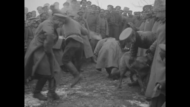cossacks gathered around men dancing energetically; one officer struggles to hold back a dog, which wants to join in; film was shot by george ercole... - austria video stock e b–roll