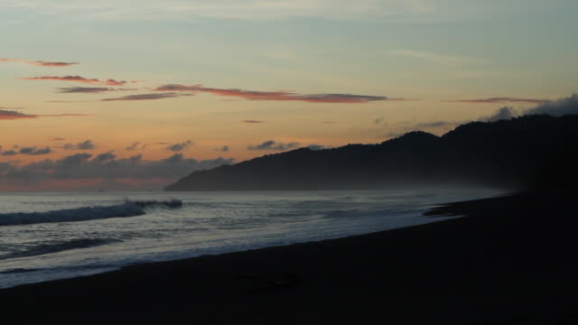 Costa Rican black sand beach at dusk with water mist