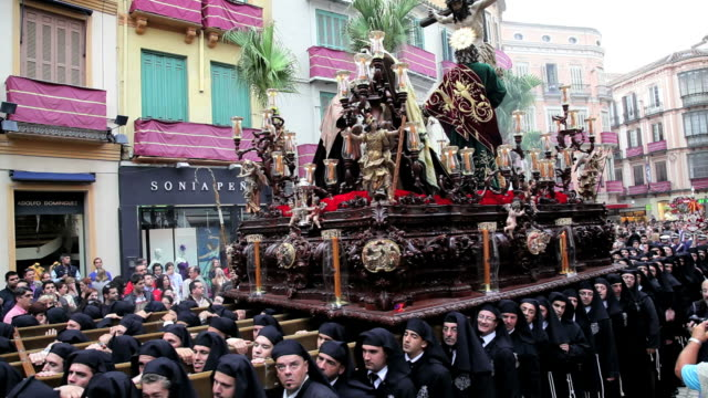 vídeos y material grabado en eventos de stock de costaleros bearing a trono a religious float during semana santa, a procession through the streets of malaga, spain, europe - semana santa