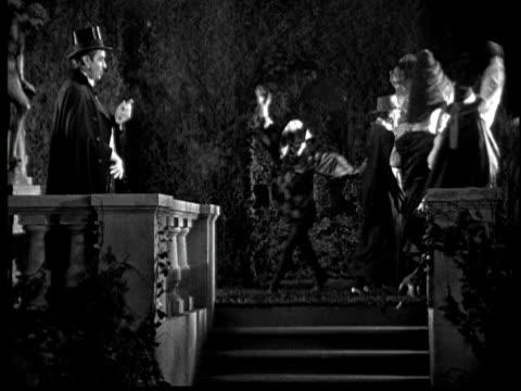 stockvideo's en b-roll-footage met 1925 ms b/w costume party in garden at night - 1925