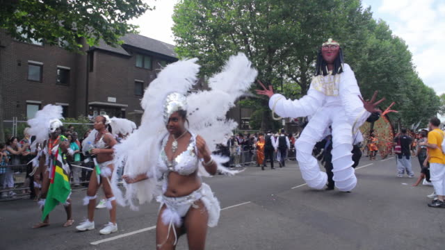 ws ds costumed dancers parade in notting hill carnival / london, united kingdom - awe stock videos & royalty-free footage