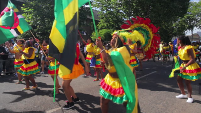 ws costumed dancers parade in notting hill carnival / london, united kingdom - flag stock videos & royalty-free footage