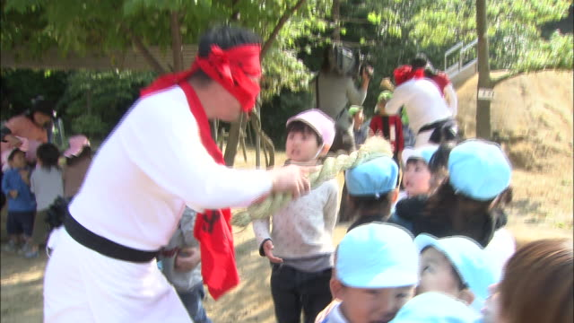 a costumed festival performer taps schoolchildren on the head during the gatchi festival in japan. - shimenawa stock videos & royalty-free footage