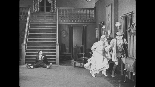 1921 costumed man and woman climb through mansion window, unaware of man (buster keaton) lying on floor - 1921年点の映像素材/bロール
