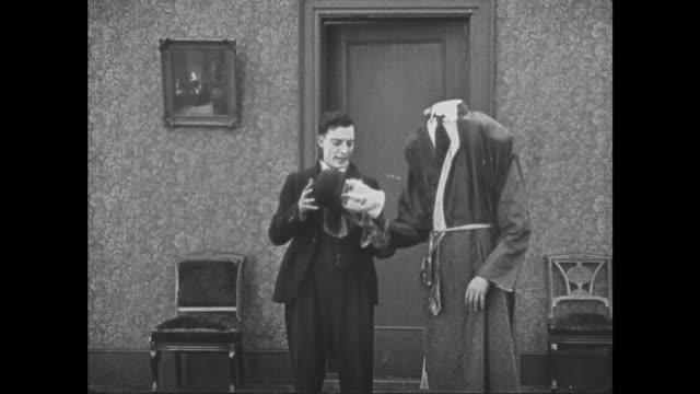 vídeos y material grabado en eventos de stock de 1921 costumed man gives his head to terrified man (buster keaton) who then sits down next to bedsheet ghost - decapitado
